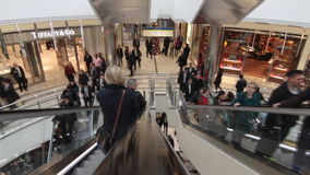 People in shopping mall. People using escalators in busy shopping mall in London, UK