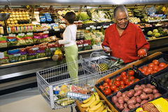 People shopping for produce. Middle aged African American man and woman in grocery store shopping for produce Royalty Free Stock Images