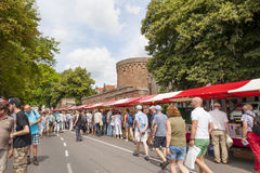 People shopping at red white book stalls. DEVENTER, THE NETHERLANDS - AUGUST 3, 2014. A long queue of market stalls with shopping people. The book stands filled Stock Photo