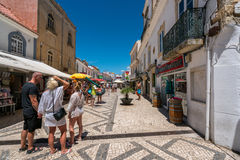 People on shopping street Portugal. Albufeira, Portugal - July 19, 2017: Perspective street view of the old parts av Albufeira city with tourists shopping and Royalty Free Stock Image