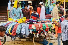 People shopping from a street seller in Bangladesh unique photo. Bangladeshi people shopping garments products from a street sales shop isolated unique photo stock images