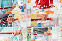 People shopping at the supermarket. People doing grocery shopping at the supermarket and pushing a shopping cart, hands close up stock photography