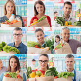 People shopping at the supermarket. Happy people shopping at the supermarket, customers and clerk holding a grocery bag filled with fresh organic vegetables stock image