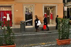 People on shopping tour in front of the dior store, rome, italy. People on a shopping tour in rome, italy, via condetti, in front of the dior store Royalty Free Stock Image