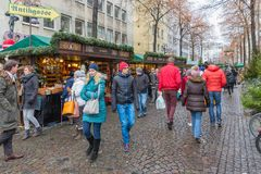 People shopping at traditional Christmas market centre Koln. KOLN, GERMANY - DECEMBER 9, 2017: Shopping people at traditional Christmas market with many stands Royalty Free Stock Photography