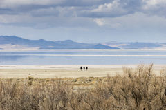 3 people on the shore of Great Salt Lake, Utah. With mountains and clouds in the background Stock Photography