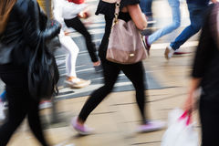 People shown in motion blur crossing a street Royalty Free Stock Photos