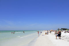 People at Siesta Beach, Florida. SIESTA KEY, FLORIDA - MAY 9, 2013: Many people relaxing at the sunny and beautiful white quartz sand Siesta Beach located in the royalty free stock image