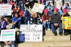 People with signs-some with hats-sitting on steps at Womens March in Tulsa Oklahoma 2018. Men and women with signs-some with hats-sitting on steps at Womens Royalty Free Stock Image