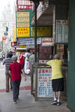 People and signs on the street in chinatown manhattan new york c Royalty Free Stock Image
