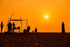 People  silhoettes at sunset on a beach Royalty Free Stock Photo