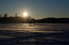 People silhouette  frozen lake snow sunset evening Stock Images