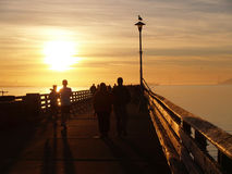 People silhouette on pier at sunset. People walking, jogging, fishing on wharf at sunset Royalty Free Stock Image