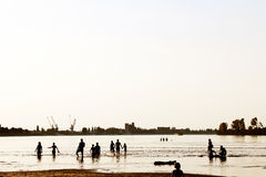 People silhouette on river beach with city industry landscape ba Stock Photo