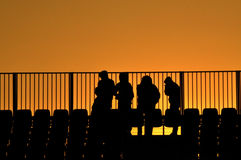 People silhouette at a stadium in the sunset Stock Photo