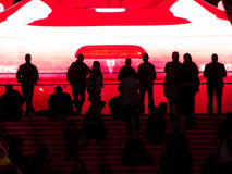 People silhouetted against huge video screen. Royalty Free Stock Images