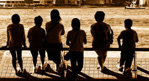 People silhouettes. Silhouettes of a family of six enjoying the harbor view at hong kong stock photo