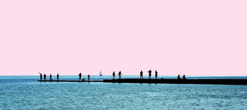 People silhouettes on a breakwater Royalty Free Stock Photo