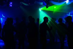 People silhouettes on dance floor of night club at event under laser lights and concert. People silhouettes on the dance floor of a night club at the event under Stock Photo