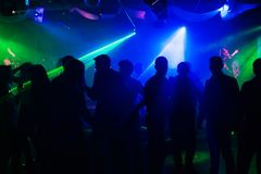 People silhouettes on dance floor of night club to laser projectors stock images