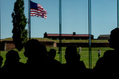 People silhouettes at fort mchenry baltimore usa flag while waving Stock Photo
