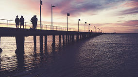 People silhouettes on Frankston pier at sunset. People silhouettes walking on Frankston Pier at sunset Stock Image