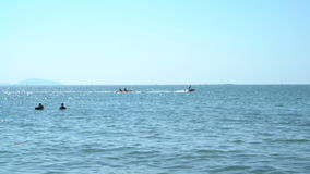People silhouettes on jet ski and banana boat stock footage