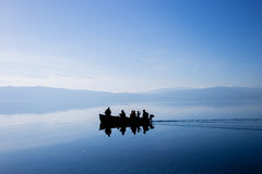 People silhouettes on a metal row boat in amazing blue water of Ohrid lake. Blue sky mirroring in crystal clear and calm water. People going fishing stock photo