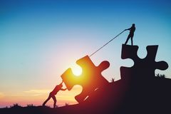 People silhouettes putting puzzle pieces together on sunlight background. Business idea concept stock photography