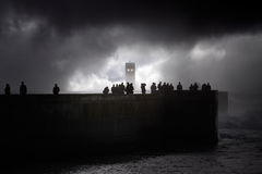 People silhouettes on the sea pier seeing storm Stock Photos
