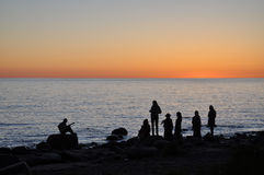 People silhouettes on the seashore at sunset. Royalty Free Stock Image