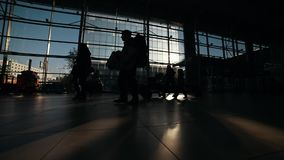 People silhouettes walking on the airport hall. Mid shot stock video footage