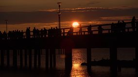 People silhouettes walking along the pier at dramatic sunset on hot summer day in Palanga beach, Lithuania. Colourful sun setting. Into Baltic sea while stock footage