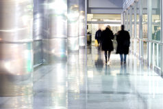 People silhouettes walking. Modern contemporary architecture concept: silhouettes of people walking through a gallery - interior of sparkling and splendid Royalty Free Stock Image