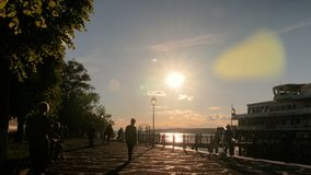 People silhouettes walking on quay. Unrecognizable people silhouettes walking on quay of old russian town Plyos. Sunset light, golden hour. Travelling concept stock footage