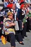 People sing war songs. A woman plays accordeon. Stock Image