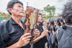 People singing the anthem and hold the portrait of Thai king Royalty Free Stock Photo