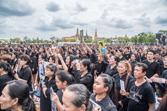 People singing the anthem and hold the portrait of Thai king Royalty Free Stock Photos
