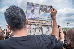 People singing the anthem and hold the portrait of Thai king Stock Photography