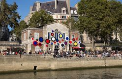 People sit along the shores of the river Seine in a sunny day in Paris, France. royalty free stock image