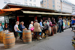 People sit around the barrels and drink wine near the small wine shop Royalty Free Stock Photo