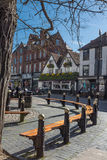 People sit on benches in the St Albans. ST ALBANS, UK - MAY 4, 2016:  People sit on benches in the scenic high street on a sunny Spring day Royalty Free Stock Photography