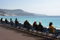 People sit on the famous blue chairs on the Promenade des Anglais, watch the azure sea and enjoy the warm sunshine. Rest and relax stock photo