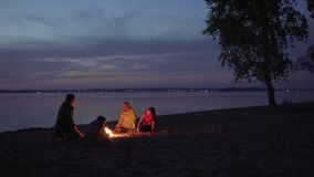 People sit by fire during family hike at beach by sea. People sit by fire during family hike at night beach by sea stock video footage
