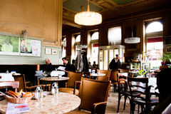 People sit inside the old stylish cafe in Vienna