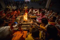 People sit near a ceremonial fire near the Holy Ganges at night. VARANASI, INDIA - MAR 22, 2018: People sit near a ceremonial fire near the Holy Ganges at night royalty free stock photography