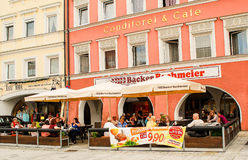 People sit outside a café on a sunny afternoon. People sit outside a café on a sunny afternoon in Neuötting,Germany,drinking coffee and having ice cream Stock Images