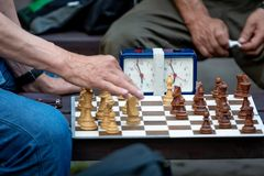 People sit in the park on benches and play chess. People sit in the park on benches and play chess Stock Image