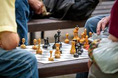 People sit in the park on benches and play chess. People sit in the park on benches and play chess Stock Images