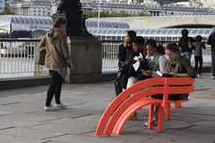People sit on a red plastic bench on the embankment on the Thames royalty free stock images